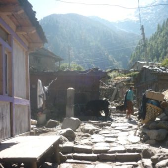 The traditional Tibetan village of Koto, a porters load resting on the right.