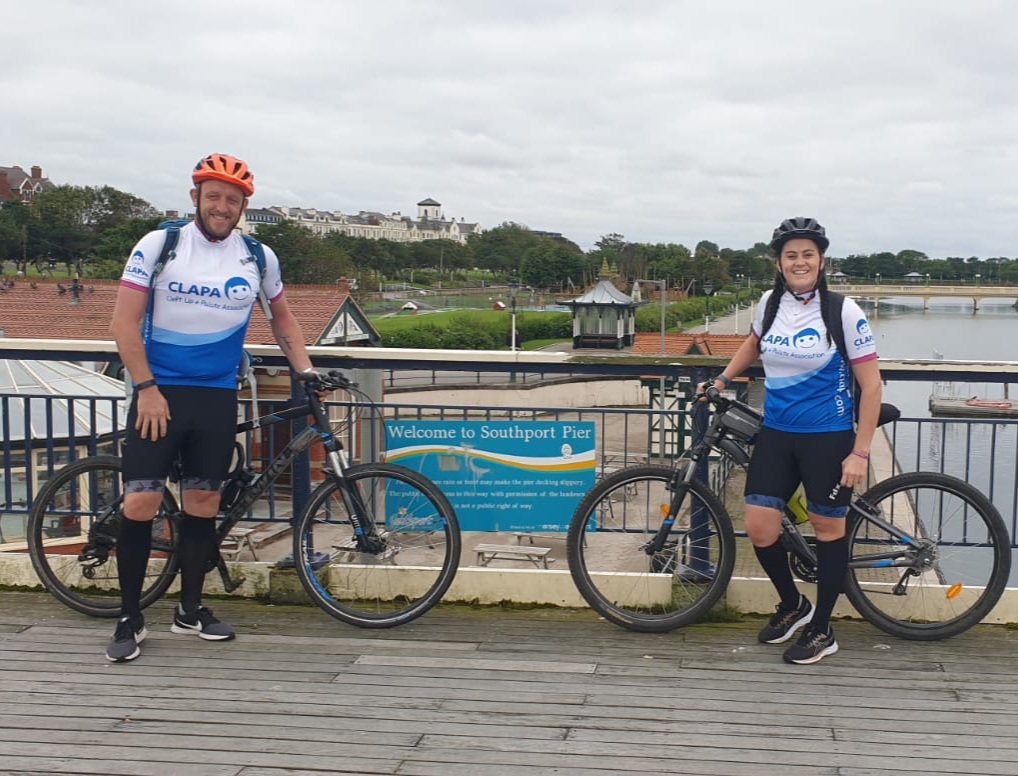 Laura and Mark are standing on a bridge by a sign that says 'Welcome to Southport Pier'. They are both standing next to their bikes and smiling at the camera.