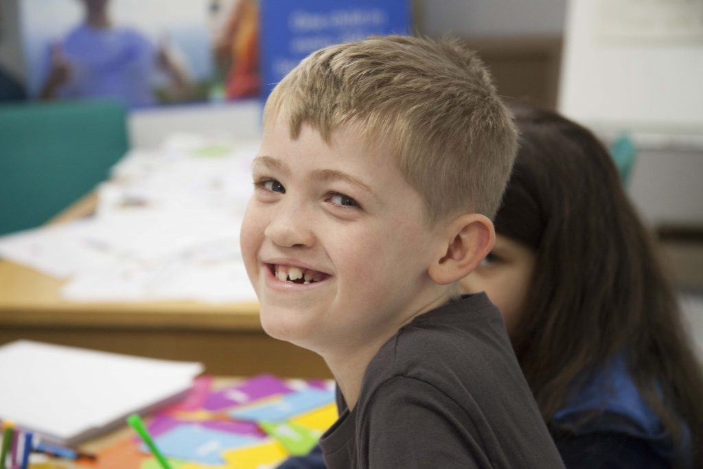 a boy smiles widely at the camera with pieces of paper and pens out of focus in the background behind him